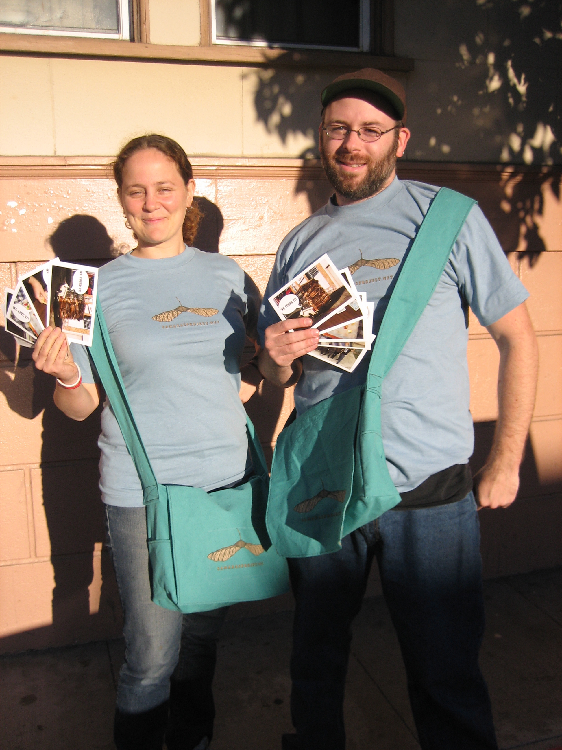 Josh MacPhee and Dara Greenwald modeling the Samaras Project Street Team gear